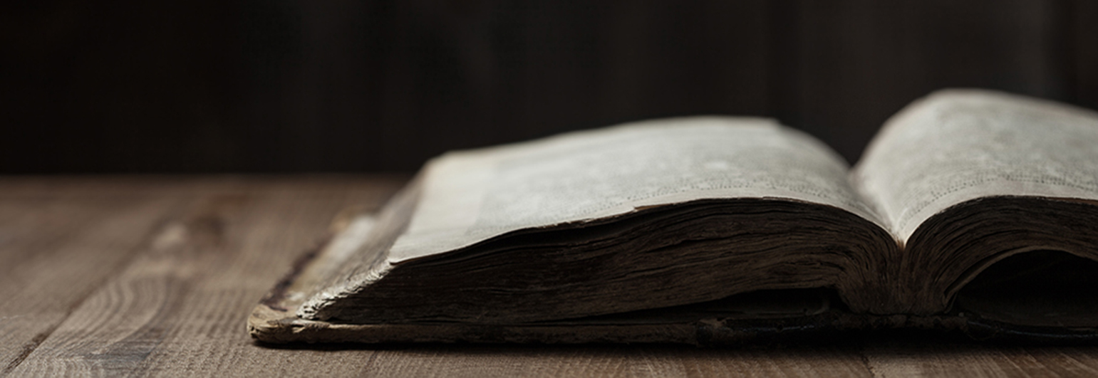 Image of a book on wooden background in a dark space